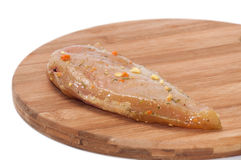 Fillet of chicken white meat on the round kitchen wooden board Stock Photo