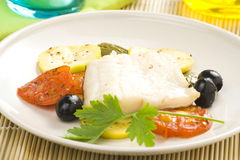 Fillet of cod baked tomatoes zucchini black olives Royalty Free Stock Photography