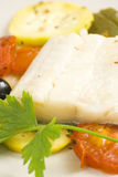 Fillet of cod baked tomatoes zucchini black olives Royalty Free Stock Image