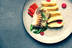 Fillet of cod with dumplings, carrots, green sweet pea and tomat stock image