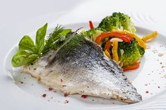 Fillet of dorado with steamed vegetables. On a white plate stock photo