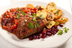 Fillet of duck with roasted potatoes, vegetables and cranberry Royalty Free Stock Photos