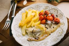 Fillet of fish with potatoes, cherry tomatoes. Royalty Free Stock Photos