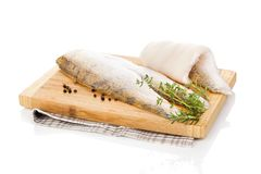 Fillet fish slices on chopping board. Fillet fish slices on wooden chopping board on white background. Luxurious seafood eating Royalty Free Stock Image