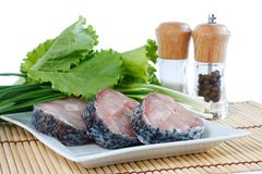 Fillet of fresh raw fish carp on a plate. With herbs lettuce, green onions and spices.  on white Stock Photo