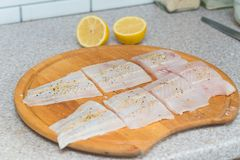 Fillet of fresh raw fish. With spices on a kitchen board Royalty Free Stock Images