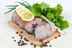 Fillet of fresh raw fish with herbs and lemon. Fillet of fresh raw fish carp on a cutting board with herbs lettuce, green onions, lemon and spicy peppers Royalty Free Stock Image