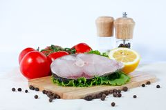 Fillet of fresh raw fish with tomatoes. Fillet of fresh raw fish on a cutting board with branch of tomatoes, lettuce, lemon and spicy peppers Stock Images
