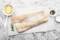 Fillet of fresh raw sea cod on a sheet of parchment on a simple light background with sea salt, ground pepper, sweet. Onion rosemary and lime slices before Stock Image