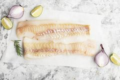 Fillet of fresh raw sea cod on a sheet of parchment on a simple light background with sea salt, ground pepper, sweet. Onion rosemary and lime slices before Royalty Free Stock Image