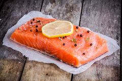Fillet of fresh salmon with pepper and lemon. On wooden rustic background Stock Photos