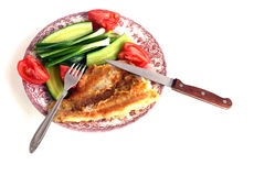 Fillet of Fried fish on a plate with cucumbers, tomatoes, onions and fork. Knife on a white background Stock Image