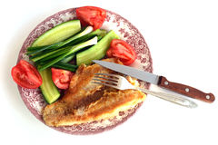 Fillet of Fried fish on a plate with cucumbers, tomatoes, onions and fork Stock Photo
