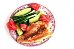 Fillet of Fried fish on a plate with cucumbers, tomatoes, onions and fork. Fillet of Fried fish on a plate with cucumbers, tomatoes, on a white background Royalty Free Stock Image