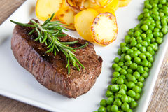 Fillet with fried potatoes and green peas Stock Images