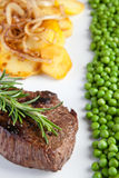 Fillet with fried potatoes,onions  and green peas Royalty Free Stock Images