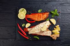 Fillet of hot smoked red snapper. S on a black stone plate with spices, herbs and sliced lemons, view from above, close-up stock photos