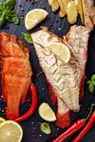 Fillet of hot smoked red snappers. Fillet of hot smoked red snapper on a black stone plate with spices, herbs and sliced lemons, vertical view from above, close royalty free stock images