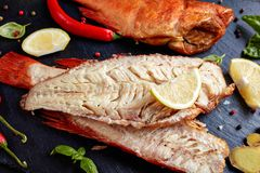 Fillet of hot smoked red snappers. Fillet of hot smoked red snapper on a black stone plate with spices, herbs and sliced lemons, view from above, close-up royalty free stock photos