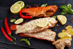 Fillet of hot smoked red snappers. Fillet of hot smoked red snapper on a black stone plate with mixed peppercorns, fresh basil leaves and sliced lemons, view royalty free stock photo