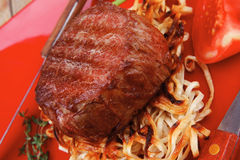 Fillet medallions on noodles with red hot chili pepper Royalty Free Stock Photo