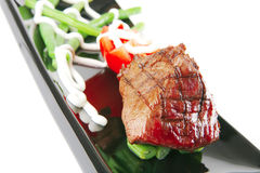 Fillet mignon on a black plate. Fillet mignon served on a white plate with tomato royalty free stock images