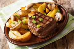 Fillet mignon with fried potatoes and mushrooms close-up on a pl. Ate on a table. horizontal stock images