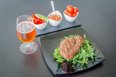 Fillet mignon grilled beef steak on black with a grass of beer and vegetables Stock Photography