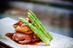 Fillet mignon steak with Foie Gras Teppanyaki dining style. Fillet mignon steak with Foie Gras and spring asparagus Japanese Teppanyaki dining style royalty free stock photo