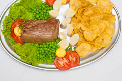 Fillet mignon steak. With peas, palmetto and chips royalty free stock photo