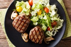 Fillet mignon steak with a salad of napa cabbage and tomatoes cl. Fillet mignon steak with a salad of napa cabbage and tomatoes and mushrooms close-up on a plate royalty free stock photos