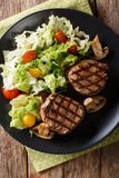 Fillet mignon steak with a salad of napa cabbage and tomatoes cl. Fillet mignon steak with a salad of napa cabbage and tomatoes and mushrooms close-up on a plate royalty free stock photo