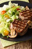 Fillet mignon steak with a salad of napa cabbage and tomatoes an. D mushrooms close-up on a plate on a table. vertical royalty free stock photography