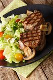 Fillet mignon steak with vegetable salad and mushrooms close-up. On a plate on a table. vertical royalty free stock image