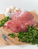 Fillet of pork (fresh meat). А piece of raw pork with ground black pepper, fresh mushrooms (champignon) and parsley lying  on baking paper Royalty Free Stock Photos