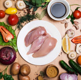 Fillet raw chicken. Fresh chicken meat on white plate on wooden. Table with fresh organic vegetables for cooking. Top view. Rustic style Royalty Free Stock Images