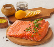 Fillet of red fish and lemon on a cutting board. DOF Royalty Free Stock Photography