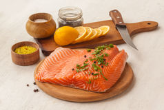 Fillet of red fish and lemon on a cutting board Stock Image