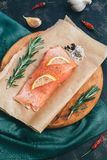 Fillet of red raw fish. Fillet of red raw fish with spices on parchment, cutting board, green napkin Stock Photography