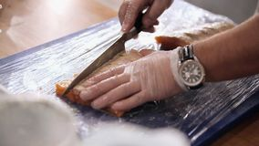 Fillet of a salmon. The cook cooks fish. Red fish. Cook`s hands close. Preparations of fish. Close up. Fillet of a salmon. The cook cooks fish. Red fish. Cook`s stock video footage