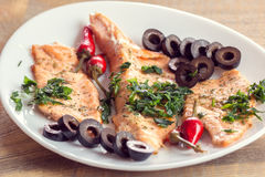 Fillet of salmon with olives, herbs and spicy red pepper Royalty Free Stock Photography