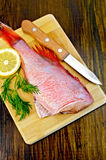Fillet of sea bass with dill and knife on board. Fillet of red grouper, dill, lemon, knife on background wooden board Royalty Free Stock Photo