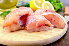 Fillet of sea bass with oil and a knife. Cut pieces of red grouper, dill, lemon, a bottle of vegetable oil, a napkin on a wooden board Royalty Free Stock Photography