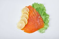 Fillet of smoked red fish with lemon and herbs, isolated white background.  Stock Image