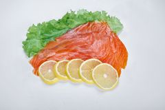Fillet of smoked red fish with lemon and herbs, isolated white background.  Royalty Free Stock Photo
