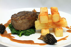 Fillet Steak with big chips. Fillet Steak chipped potatoes, spinach and morel mushroom sauce Stock Images