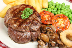 Fillet Steak and Chips. Juicy fillet steak with chips, mushrooms, peas and onion rings Royalty Free Stock Images