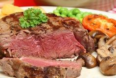 Fillet Steak Dinner. Rare fillet steak with chips, peas & mushrooms Stock Photos