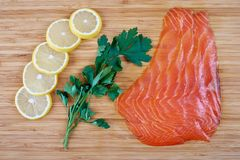 Fillet trout with fresh herbs and lemon on a board. Seafood Stock Photography