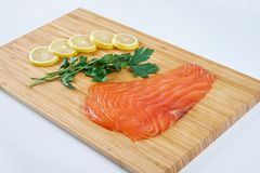 Fillet smoked trout with fresh herbs and lemon on a board. Seafood, isolated. Fillet trout with fresh herbs and lemon on a board. Seafood Stock Image
